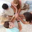 Teenagers lying on the floor with hands together — Stock Photo #10278356