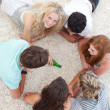 Group of teenagers playing spin bottle on floor — Stock Photo #10278373