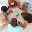 Group of teenagers playing with a bottle on the floor — Stock Photo