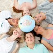 Teenagers on the floor with a terrestrial globe in the center — Stock Photo