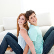 A smiling couple of teenagers sitting on the floor — Stock Photo #10278527