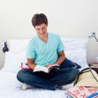 Smiling teenager reading a book in his bedroom — Stock Photo #10278571