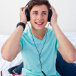 A teenage guy sitting on his bed listening to the music — Stock Photo