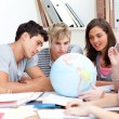 Teenagers in a library working with a terrestrial globe — Stock Photo