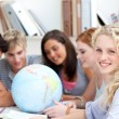 Teenagers in a library working with a terrestrial globe - Stockfoto