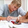 Teen guy studying in the library - Stock Photo