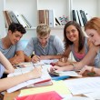 Smiling teenagers studying in the library — Stock Photo