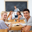 Stock Photo: Teenagers studying together in class