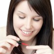 Attractive woman painting her nails — Stock Photo