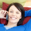 Charming teen girl talking on phone lying on a sofa — Stock Photo #10279207