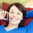 Charming teen girl talking on phone lying on a sofa — Stock Photo