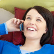 Happy teen girl talking on phone lying on a sofa — Stock Photo