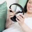 Cheerful young woman putting headphones lying on a sofa — Stock Photo #10279460