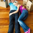 Couple sleeping on the floor. Moving house - Stock Photo