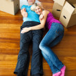 Couple lying on the floor with thumbs up. Moving house — Stock Photo