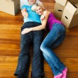 Stock Photo: Couple lying on the floor with thumbs up. Moving house