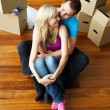 Stock Photo: Happy young couple sitting on floor. Moving house