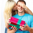 Woman giving a present and a kiss to a man — Stockfoto