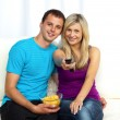 Happy couple watching television and eating crisps - Stock Photo