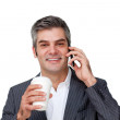 Smiling Businessman on phone while drinking a coffee — Stock Photo