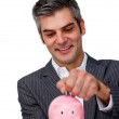 Assertive Businessman saving money in a piggybank — Stock Photo #10279623