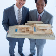 Architects holding a model house — Stock Photo