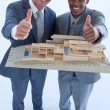Architects holding a model house with thumbs up — Stock Photo
