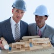 Close-up of architects holding a model house in office - Stock Photo