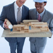 Engineers with hard hats holding a model house — Stock Photo