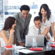 Multi-ethnic business team working together with a laptop — Stock Photo