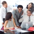 Royalty-Free Stock Photo: Smiling multi-ethnic business team working with a laptop