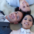Business team on floor with heads together smiling — Stock Photo