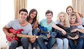 Группа подростков играл на гитаре на дому — Стоковое фото