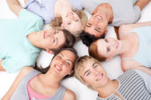 Friends lying on floor with heads together — Stock Photo