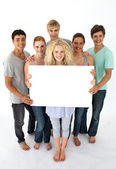 Group of teenagers holding a blank card — Stock Photo