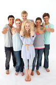 Group of teenagers standing in front of the camera with thumbs u — Stock Photo