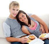 Teen couple eating burgers and fries at home — Stock Photo