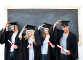 Group of teenagers celebrating after Graduation — Stock Photo