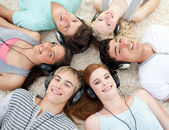 Group of friends listening to music on the floor — Stock Photo