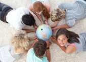 Group of friends on the floor examining a terrestrial world — Stockfoto