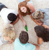 Group of friends playing spin the bottle on the floor — Stock Photo