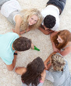 Group of teenagers playing spin the bottle on the floor — Stock Photo