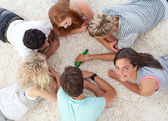 Group of friends playing spin the bottle — Stock Photo