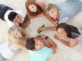 Group of teenagers playing spin the bottle — Stock Photo