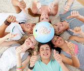 Teenagers on the floor with a terrestrial globe in the center an — Stock Photo
