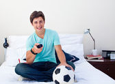 Teen guy watching a football match in television — Stock Photo