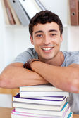 Smiling teeenager studying lots of books — Stock Photo