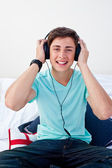A teenage guy listening to the music in his bedroom — Stock Photo