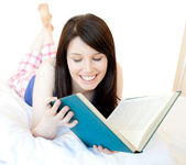 Portrait of a confident teen girl studying lying on a bed — Stock Photo