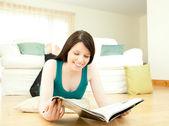 床に横たわって雑誌を読む女性の笑みを浮かべてください。 — ストック写真